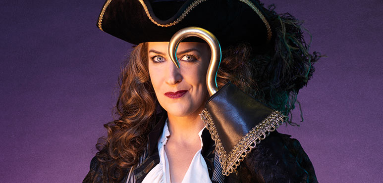 image of a woman dressed as Captain Hook, holding her hook near her eye menacingly.